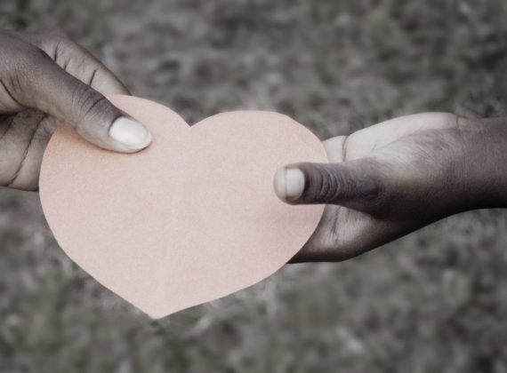 two hands sharing a heart