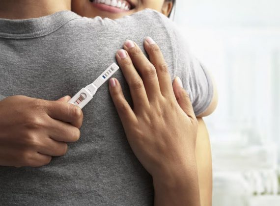 Joyful couple with positive pregnancy shown in the test device